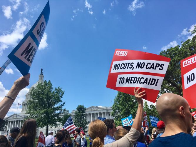 a group of people hold signs that read NO CUTS NO CAPS TO MEDICAID! in front of the United States Capitol