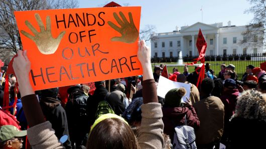 a sign that says HANDS OFF OUR HEALTHCARE is held in a crowd in front of the White House