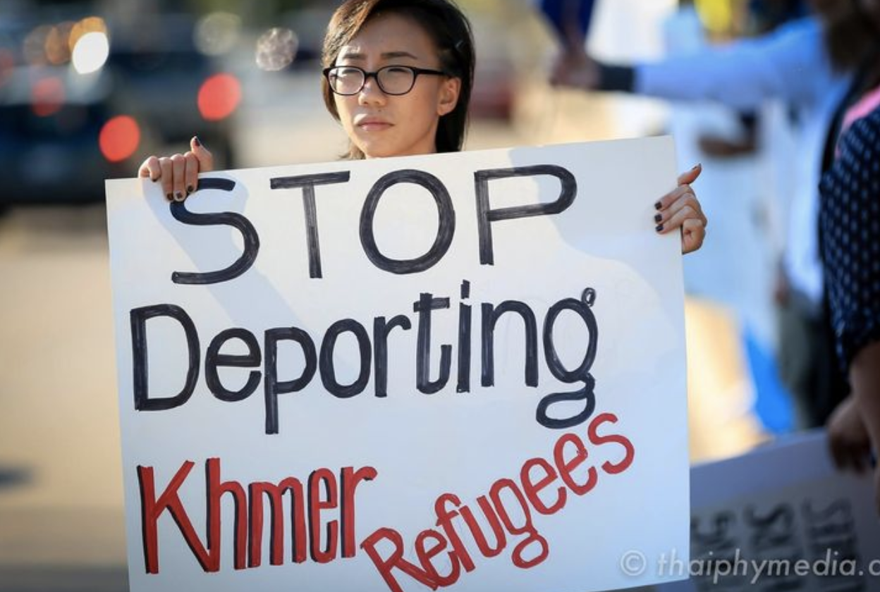 A young person holds a sign that says STOP Deporting Khmer Refugees