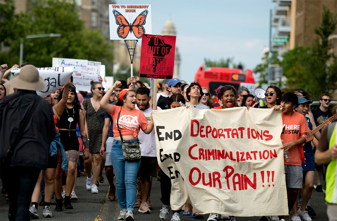 A crowd walks down a city street. In the front is a banner that reads End Deportations, End Criminalization, End our Pain!