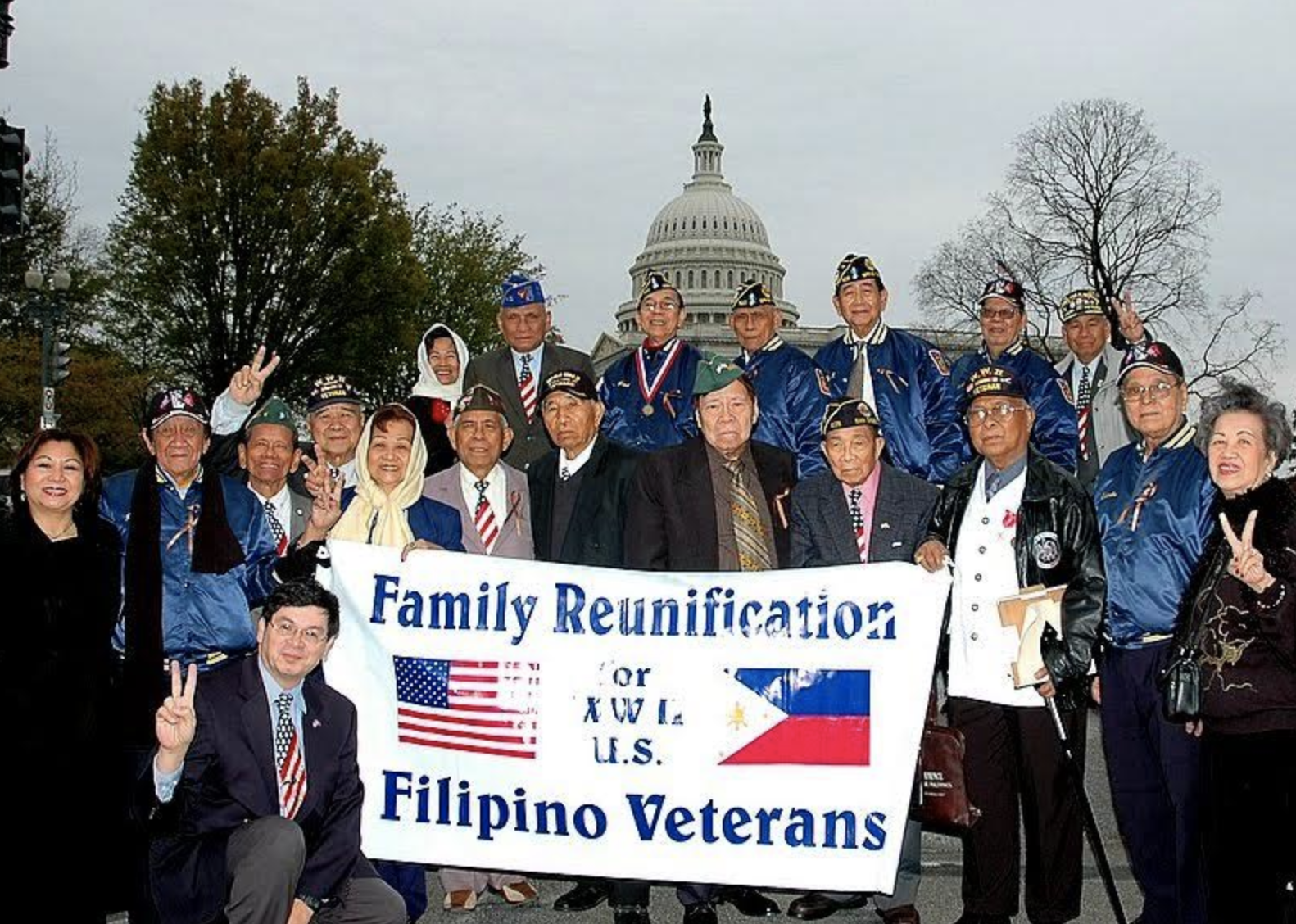 Filipino Veterans of World War Two pose in front of the United States Capitol with a banner that reads FAMILY REUINIFICATION FOR WWII US FILIPINO VETERANS